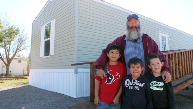 Haskell Hall, resident of Tularosa, stands with his grandsons Isaiah and Josiah Galban and their friend Tane Taiaroa in front of Hall's new home in Tularosa. The home is part of White Sands Habitat for Humanity's rehabilitation program and was made possible by help from the Otero County community.