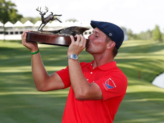Bryson DeChambeau kisses the trophy after winning the