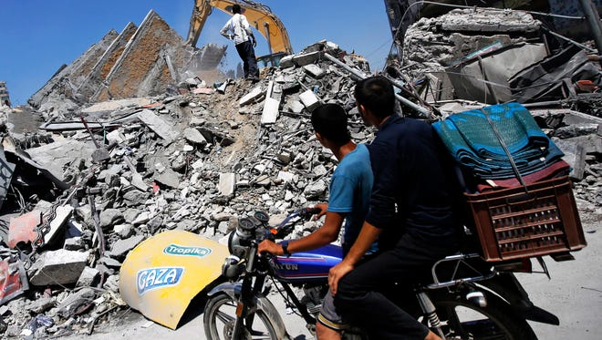 Palestinians inspect the rubble of destroyed Al-Basha tower in Gaza City on Aug. 26, 2014.