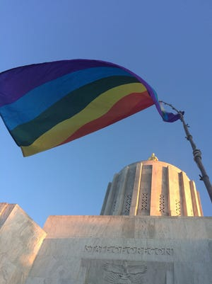 Supporters hoist a gay pride flag in the air at the Oregon State Capitol during a 2016 Salem Candlelight Vigil.