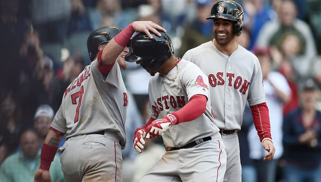 Mookie Betts of the Boston Red Sox is congratulated by Christian Vazquez ((left) following a ninth-inning home run against the Milwaukee Brewers at Miller Park on Thursday.