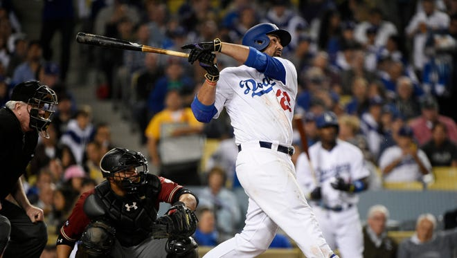 Los Angeles Dodgers' Adrian Gonzalez follows through on a solo home run off Arizona Diamondbacks' Rubby De La Rosa, while catcher Welington Castillo, left, watches during the fourth inning of a baseball game in Los Angeles, Wednesday, April 13, 2016.