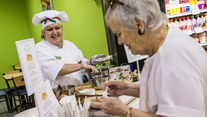 Food demonstrator Tricia Cogan serves samples of pork piccata to customer Elizabeth Keyse of Naples at Publix in East Naples on Friday, Feb. 24, 2017. Cogan has been with Publix for four years and often dresses up to match the theme of whatever food she is serving that day.