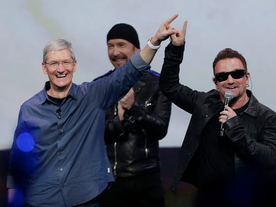 Apple CEO Tim Cook, left, smiles next to U2 members, The Edge, Bono, and Larry Mullen Jr. during a 2014 event in Cupertino, Calif.