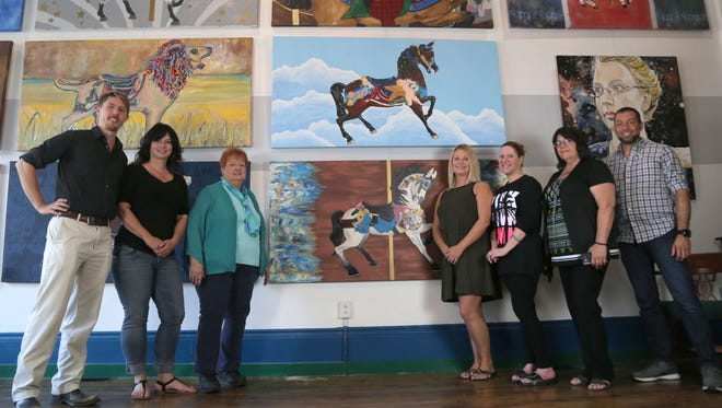 Luke Beekman, Robin Wilson, Sandy Laipply, Allison Pence, Yvonne Zenisek, Victoria Hoefler and Ivan Pellot, from left, stand next to paintings of animals featured on the Richland Carousel l.