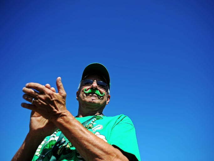 Decked out in green, including a fake green mustache, Richard Riley, of Madison, S.D., claps along as the Connolly Irish Dancers perform during the 2014 Dakota Irish Fair on Saturday, July 26, 2014, at Falls Park West in downtown Sioux Falls, S.D.