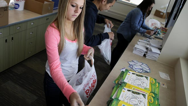 Hope Dercks organizes items for goodie bags during a training session Tuesday at the Boys & Girls Club of Menasha. The bags will be given to people attending the open house on Saturday.