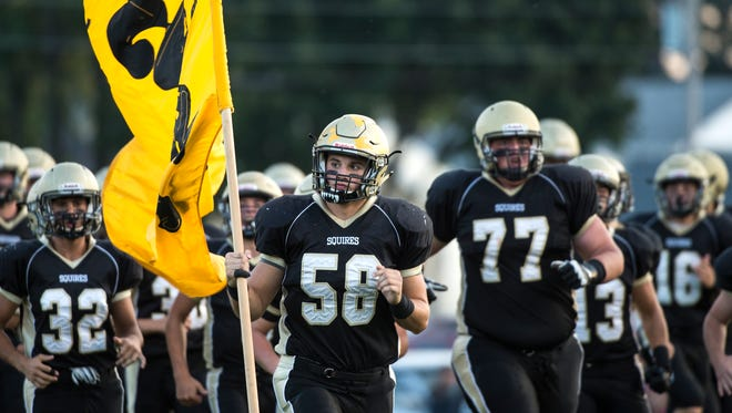 Delone's Zack Schussler (58) carries out part of Delone's banner, Friday, September 15, 2017. The Squires defeated the Colonials, 44-19.