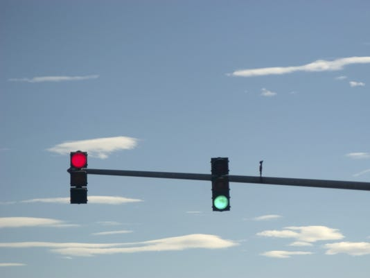 Red And Green Traffic Lights Hanging In A Blue Sky