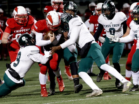 Clinton Twp. Chippewa Valley quarterback Tommy Schuster is stopped by the defense of Detroit Cass Tech during the game at Chippewa Valley on Friday, Nov. 10, 2017.
