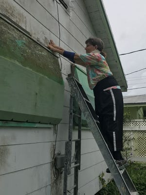Connie Tucker secures her home on 31st Street in Palm City the morning of Sept. 9 before the arrival of Hurricane Irma.