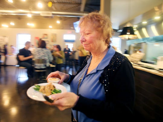 Jeanene Bohman of Detroit enjoys the tastings during the Detroit Free Press Feast Thanksgiving tasting event at the Great Lakes Culinary Center in Southfield.