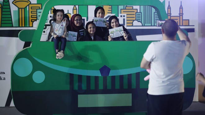 Teenaged girls pose behind a pretend car while they old up certificates for completing an outdoor educational driving event for women in Jeddah, Saudi Arabia. Saudi Arabia is scheduled to lift its ban on women driving.