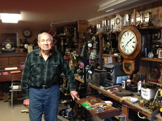 Jimmy Hayes stands in his self-built shop surrounded by 200 or more clocks.
