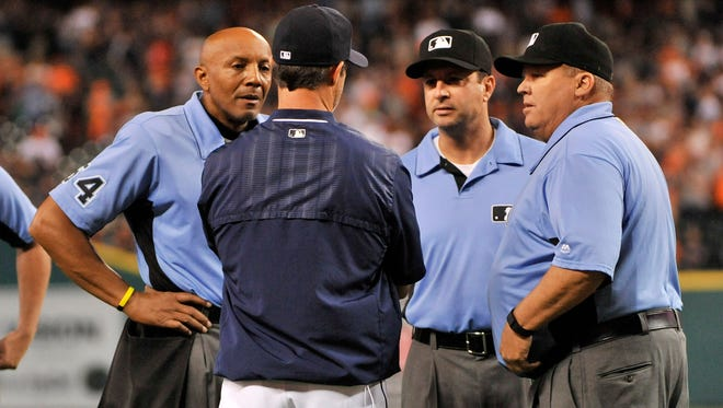 Tigers manager Brad Ausmus consults with the umpires after the Miguel Cabrera flies into a double play and Cameron Maybin is doubled off first to end the game.