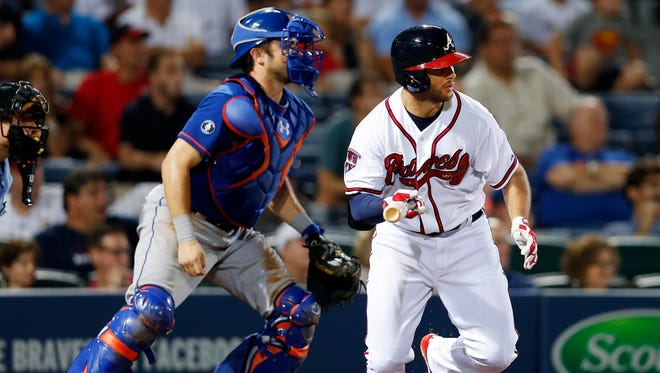 Atlanta's Tommy La Stella, right, ties the game with a two-run single in the eighth inning as Mets catcher Travis d'Arnaud looks on in Atlanta on Monday.
