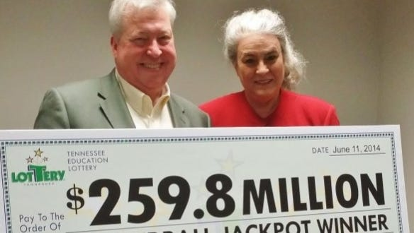 Roy Cockrum of Knoxville, Tenn., left, holds check presented by Tennessee Education Lottery CEO Rebecca Hargrove after winning the Powerball jackpot in 2014. He has recently been designated as one of Tennessee's 11 presidential electors by the state Democratic Party.