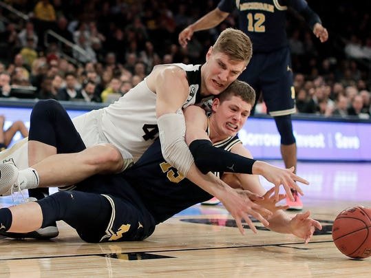 Purdue center Isaac Haas (44) and Michigan forward Moritz Wagner (13) scramble for a loose ball during the first half of the NCAA Big Ten Conference tournament championship college basketball game, Sunday, March 4, 2018, in New York. (AP Photo/Julie Jacobson)
