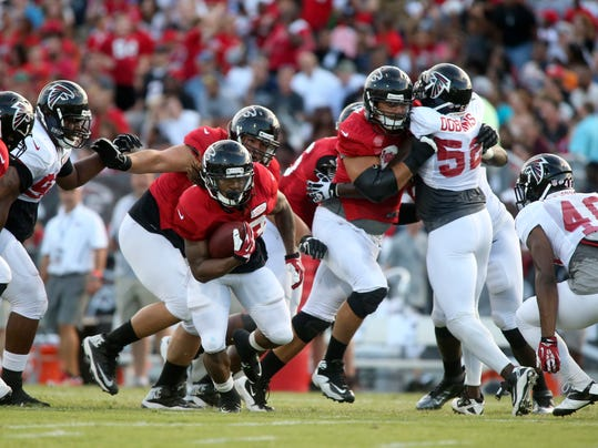 Atlanta Falcons running back Devonta Freeman (33) carries the ball during Friday Night Lights, at Archer High School on Friday, Aug. 1, 2014, in Lawrenceville, Ga. The Falcons continued their tradition of staging a practice at an area high school each year. (AP Photo/Jason Getz)