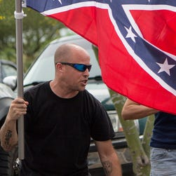 A Confederate flag supporter, left, and a counter-protester clashed near a Walmart in Phoenix on Sunday, July 5, 2015.