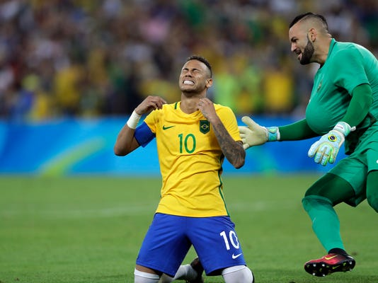 Brazil's Neymar cries as he kneels down to celebrate with teammate goalkeeper Weverton after scoring the decisive penalty kick during the final match of the men's Olympic football tournament between Brazil and Germany at the Maracana stadium in Rio de Janeiro, Brazil, Saturday Aug. 20, 2016. Brazil won the gold medal on  a penalty shootout. (AP Photo/Andre Penner)