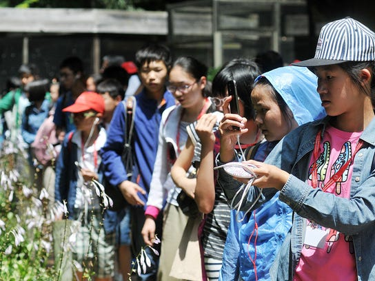 Students from Shanghai, China, snap photos of flowers and fowl at the Ohio Bird Sanctuary in July 2015.