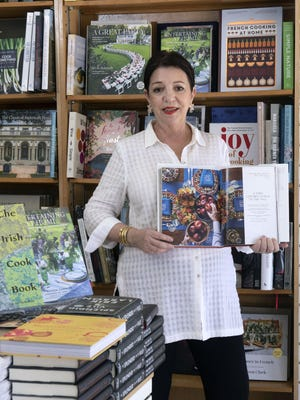 """Candice Cohen, owner of the Palm Beach Book Shop, with a copy of """"Le Manoir Aux Quat'Saisons."""" It's a $375.00 super coffee table book filled with stunning photos. Plus a shot of several entertaining and cooking books."""
