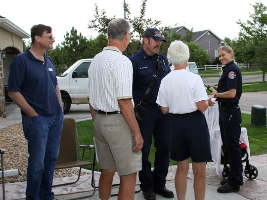 Emergency medical technicians Mike Edwards, Cara Dunsmoor and Craig Fisher visit with Mark Seaman and Ron and Lynn Leader during a National Night Out barbecue Tuesday on Sandy Lane in Windsor. Hundreds of residents celebrated the night with barbecues, ice cream socials and other gatherings to reinforce the importance of neighbors in ensuring security and community awareness.