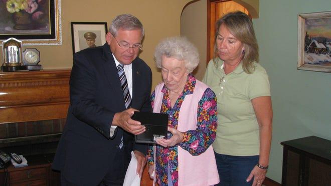 U.S. Sen. Robert Menendez presents medals to Chester Banasiak's widow, Josie, and daughter, LuAnn Osborn.