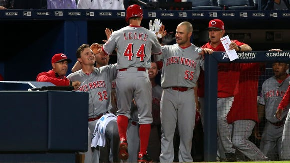 Mike Leake is congratulated by Jay Bruce and Skip Schumaker after his home run Thursday in Atlanta.