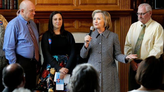 Democratic presidential candidate Hillary Rodham Clinton speaks during a gathering at the home of Dean Genth, left, and Gary Swenson, right, Monday, May 18, 2015, in Mason City, Iowa.