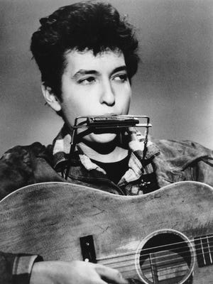 Folk singer and songwriter Bob Dylan plays the harmonica and acoustic guitar in March 1963.