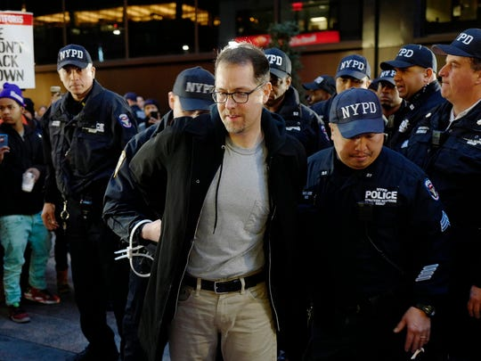 A man is arrested by police officers after he and other protesters blocked Broadway in front of a McDonald's restaurant, Tuesday, Nov. 29, 2016, in New York. About 25 chanting minimum-wage protesters were arrested. They were among about 350 people at a peaceful rally early Tuesday. The event was part of the National Day of Action to Fight for $15. The campaign seeks higher hourly wages, including for workers at fast-food restaurants and airports.
