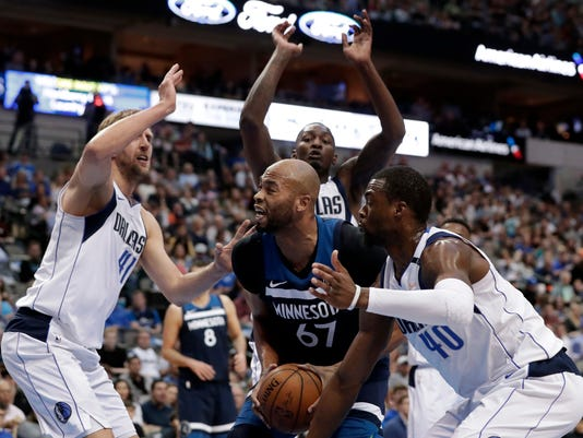 Minnesota Timberwolves forward Taj Gibson (67) works to shoot as Dallas Mavericks' Dirk Nowitzki, left, Dorian Finney-Smith, rear, and Harrison Barnes (40) defend in the first half of an NBA basketball game in Dallas, Friday, March 30, 2018. (AP Photo/Tony Gutierrez)