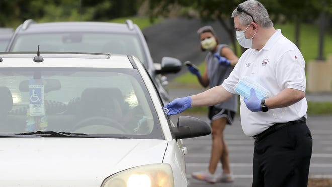 With a statewide mask order now in effect, state health officials caution that it will take time before it results in a downward trend in coronavirus cases. Meanwhile, Tuscaloosa Fire Rescue Chief  Randy Smith, seen here distributing masks to motorists earlier this month, said more than 20 firefighters have been diagnosed with the disease. However, this has not hurt the department's ability to respond to calls and emergencies, he said.