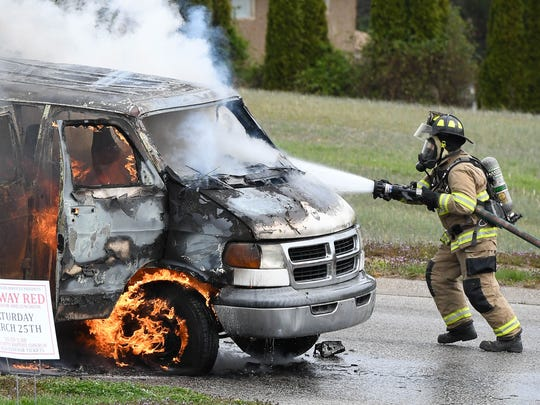 A Henderson City Fireman uses a water hose to extinguish a burning church van that was being used to shuttle passengers to a charity fundraiser at Community Baptist Church Saturday. No one was injured in the fire, but the 15-passenger van was destroyed and a nearby car was damaged, March 25, 2017.
