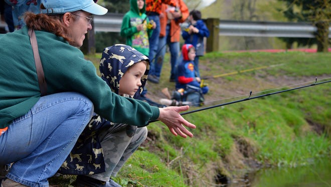Traci Meredith helps her son, Barrett, fish for trout during a Family Fishing Day event held by the Oregon Department of Fish and Wildlife.