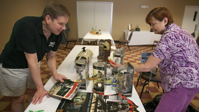 "Toy collector and dealer Joel Magee, who is known as ""America's Toy Scout,"" looks on as Eileen Pollara, Penfield, unpacks a large collection of Star Wars toys she brought to the Rochester Vintage Toy Buying Show at the Holiday Inn in Henrietta Saturday, June 25, 2016."