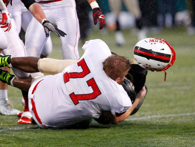Hilton's Jake Reed, front, loses his helmet while tackling R-H's DeKwon Wilson.