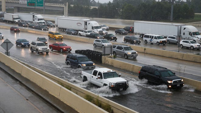 Cars drive through high water on the exit ramp to southbound 610 from eastbound Interstate-10 on Wednesday, July 4, 2018, in Houston. Heavy rains that flooded some Houston streets on July Fourth are expected to subside. (Michael Ciaglo/Houston Chronicle via AP) ORG XMIT: TXHOU203