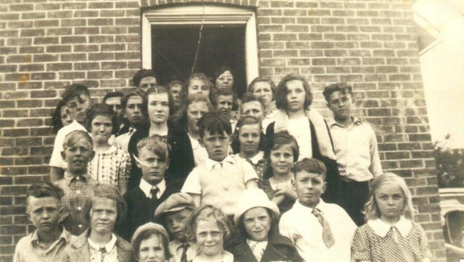 A photo shows the students attending the Black Creek School in 1938. The teacher, Mrs. Kratz, is at the rear of the photo and is framed in the open door.