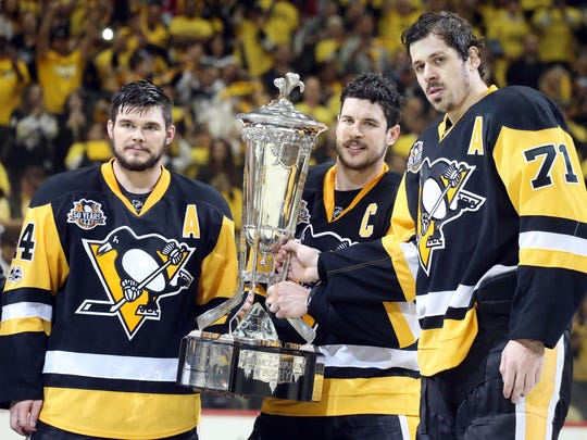 Pittsburgh Penguins left wing Chris Kunitz (14) and center Sidney Crosby (87) and center Evgeni Malkin (71) hold the Prince of Wales trophy as as champions of the Eastern Conference after the Pens defeated the Ottawa Senators in double overtime of game seven of the Eastern Conference Final of the 2017 Stanley Cup Playoffs at the PPG PAINTS Arena.
