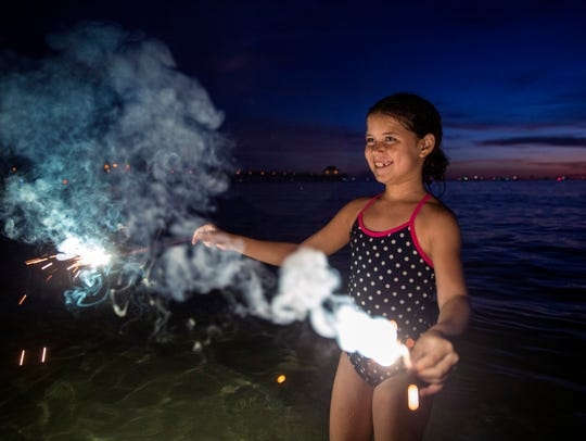 Bryanna Maher, 8, plays with a sparkler in the water