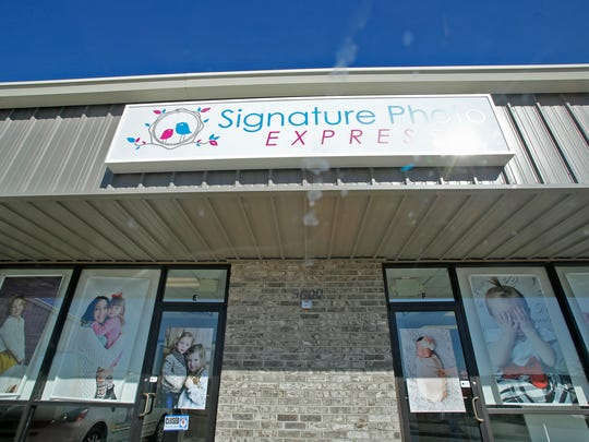 A sign for Signature Photo Express is pictured Thursday in Farmington.