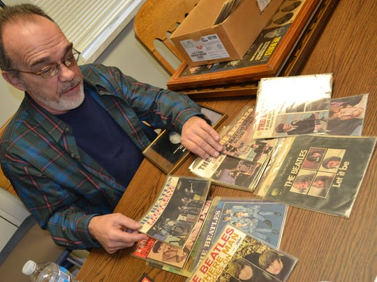 """Grindstaff with some of the valuable 45 record sleeves he kept from records he purchased through the years. """"Lots of people keep the records and throw the sleeves away,"""" he said."""