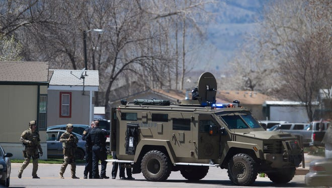 Law enforcement personnel crowd around a Bearcat tactical vehicle as they respond to a shooting at the Collins Aire Mobile Home Park on Saturday, April 14, 2018.