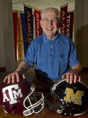 SEC commissioner Mike Slive poses with helmets of Missouri and Texas A&M, when the schools joined the league in 2012.