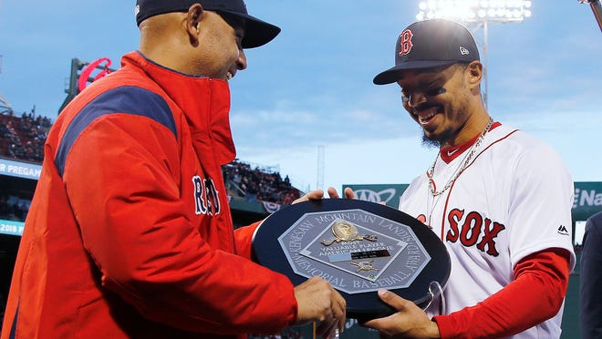 FILE - In this April 11, 2019, file photo, Boston Red Sox manager Alex Cora, left, presents right fielder Mookie Betts with the 2018 AL MVP Award before a baseball game between the Red Sox and the Toronto Blue Jays at Fenway Park in Boston. The award includes the name and image of Kenesaw Mountain Landis.