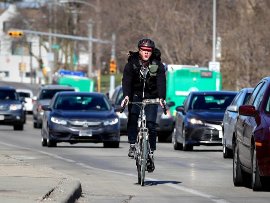 A bicyclist rides over the Milwaukee River on Locust