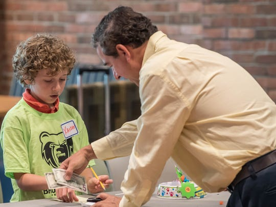 Xander Yoder learns about free enterprise as he counts money at a young entrepreneurs event at Kellogg Community College on Wednesday.